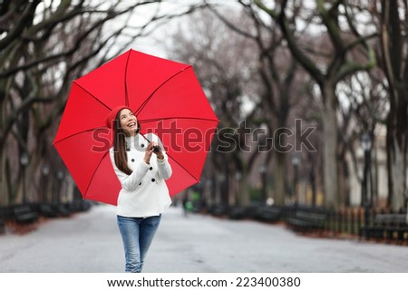Woman with red umbrella walking in park in fall. Happy smiling multiracial girl walking cheerful with red umbrella in Central Park, Manhattan, New York City, USA. - stock photo