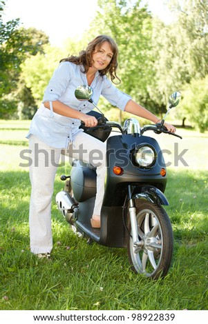 Woman with retro motorbike scooter