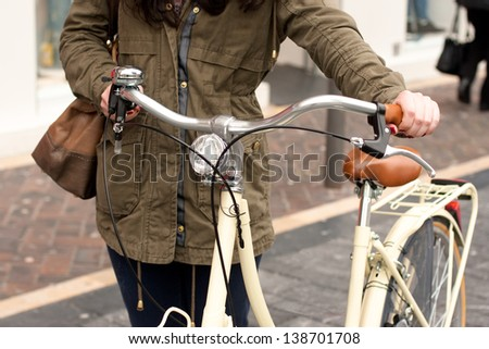 Woman with retro style bicycle walking down the street in the city - stock photo