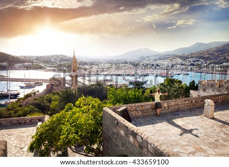 Woman with rising hands on the Bodrum Castle near Aegean Sea with yachts at sunset - stock photo