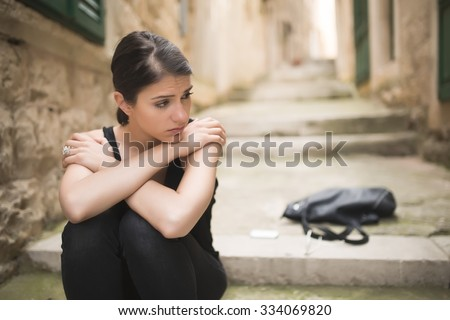 Woman with sad face crying.Sad expression,sad emotion,despair,sadness.Woman in emotional stress and pain.Woman sitting alone on the stairs, after a fight with a boyfriend.Relationship and love problem - stock photo