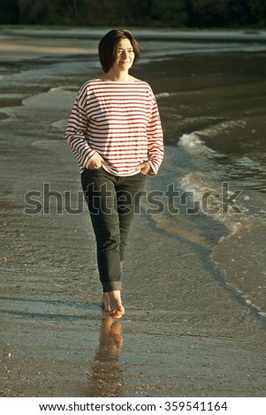 woman with sailor shirt and jeans walking on the beach at sunset