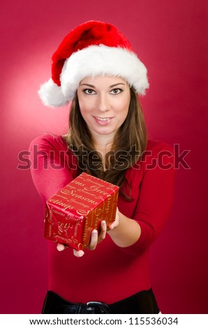 Woman with santa hat giving a christmas gift box on a red background - stock photo