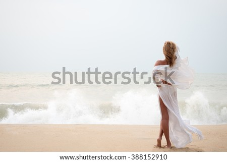 Woman with sarong on the beach on a stormy day