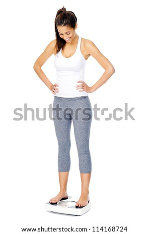 Woman with scale celebrating weightloss and a healthy fit body - stock photo