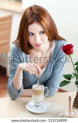 Woman with scarlet rose sitting at the cafe - stock photo