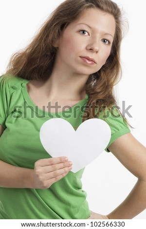 Woman with serious look holding white heart in one hand - stock photo