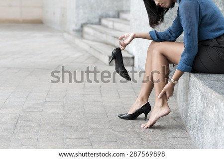 Woman with shoe sitting outdoors and massaging ankle - stock photo