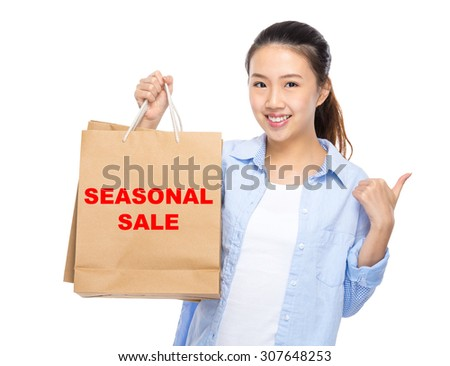 Woman with shopping bag and thumb up for showing seasonal sale