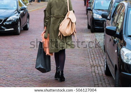 woman with shopping bag walking on a street in the city