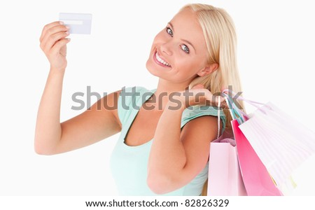 Woman with shopping bags and a credit card in a studio - stock photo