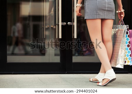 Woman with shopping bags at the mall doorway - stock photo