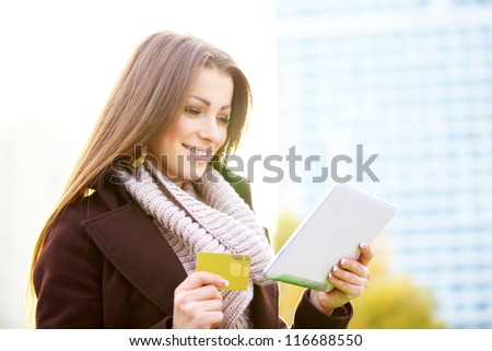 woman with shopping bags digital tablet and credit card outdoor. Making online shopping concept