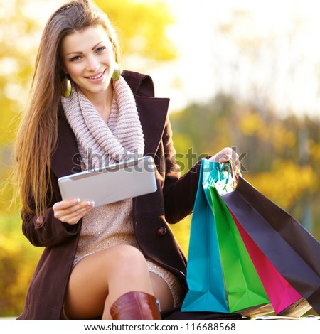 woman with shopping bags digital tablet outdoor - stock photo