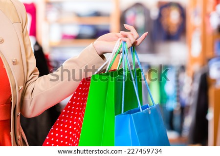 Woman with shopping bags in shop - stock photo