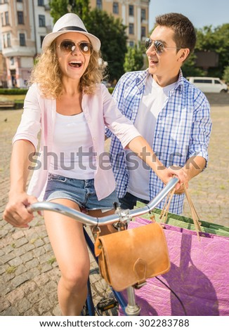 Woman with shopping bags riding on bicycle and man standing near her. - stock photo