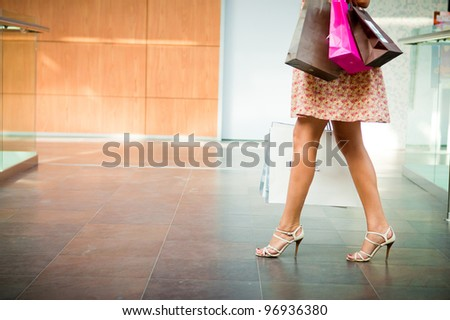 woman with shopping bags, smiling and walking - stock photo