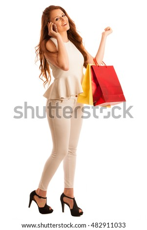 Woman with shopping bags talking on smart phone after a successful purchase on the sale isolated over white