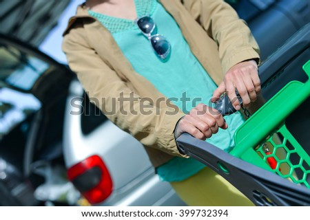 Woman with shopping cart on car parking - stock photo