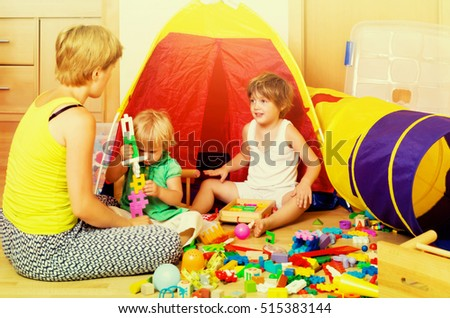 Woman with short hair and two siblings together playing with  toys in  interior