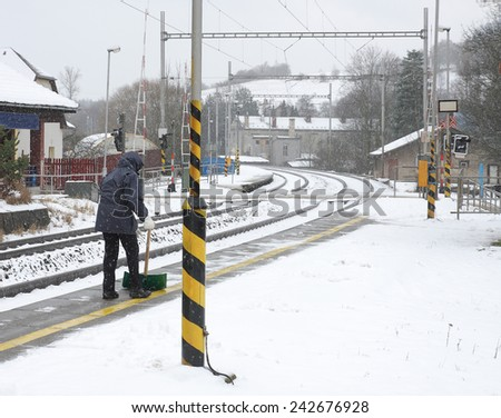 Woman with shovel clears snow from a platform on the  station - stock photo