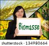 Woman with sign and the german word biomass / biomass - stock photo