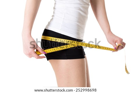 Woman with slimming body measuring her perfect butt and hips. Healthy lifestyle concept. - stock photo