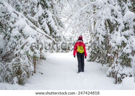 Woman with small backpack walking alone in snowy winter forest