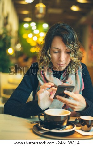 woman with smart phone in coffee shop - stock photo