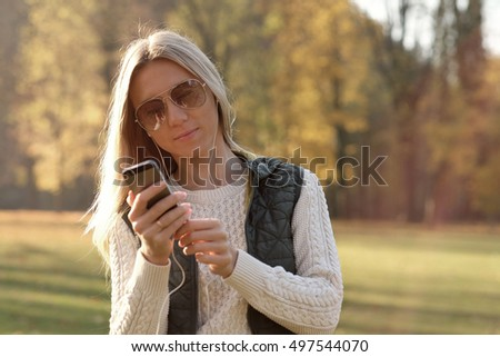 Woman with smartphone in autumn park outdoor.