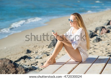 Woman with smartphone sitting on the beach at the sea background