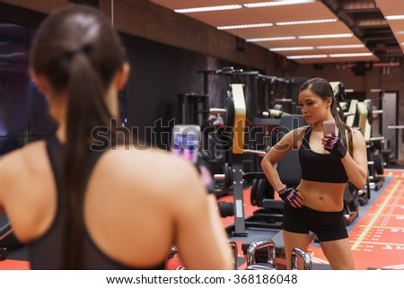woman with smartphone taking mirror selfie in gym - stock photo