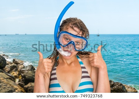 Woman with snorkeling mask for diving stands on beach in front of the sea