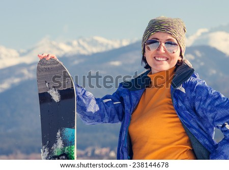 Woman with snowboard on the mountain hill view  - stock photo