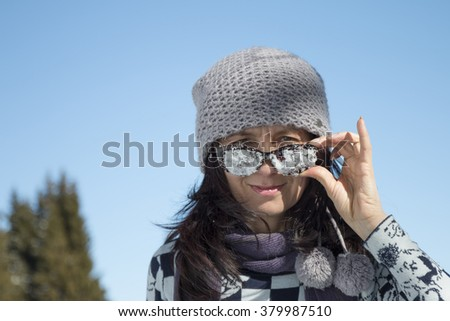 Woman with snowy sunglasses against the blue sky - stock photo