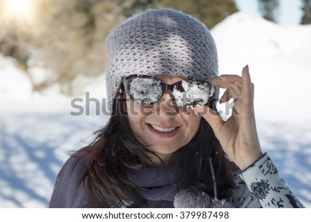 Woman with snowy sunglasses in the winter mountain - stock photo