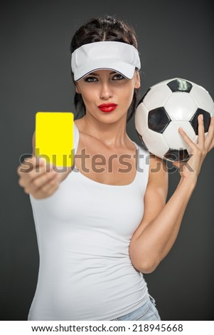 Woman with soccer ball referee with yellow card - stock photo