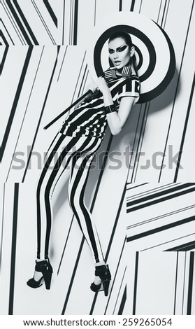 woman with spiral umbrella on striped background in studio - stock photo