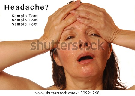 Woman with splitting headache holding hands on forehead, with sample text - stock photo