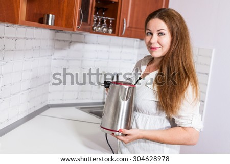 Woman with steel electric tea kettle in hands, copy space in front of - stock photo