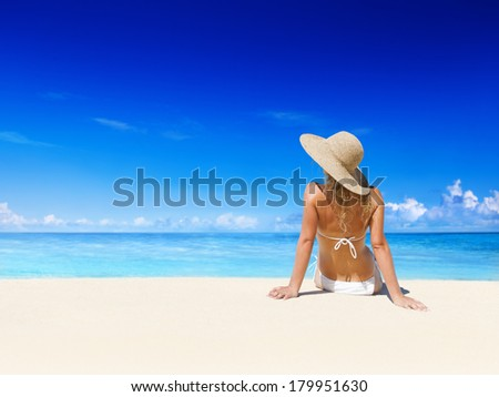 Woman with Straw Hat Relaxing On a Beach - stock photo