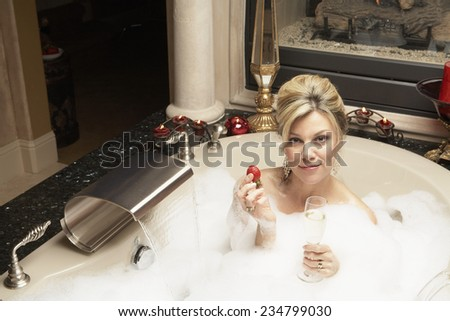 Woman With Strawberry and Champagne in Bubble Bath - stock photo
