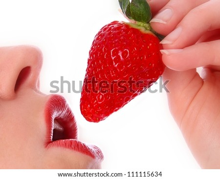 Woman with strawberry on her red lips - stock photo