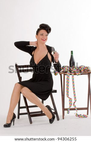 Woman with streamers and champagne sitting at the table when celebrating / Cheers - stock photo