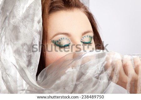 Woman with striking makeup conceals her face - stock photo