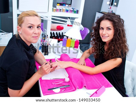 woman with stylist on manicure treatment in beauty salon