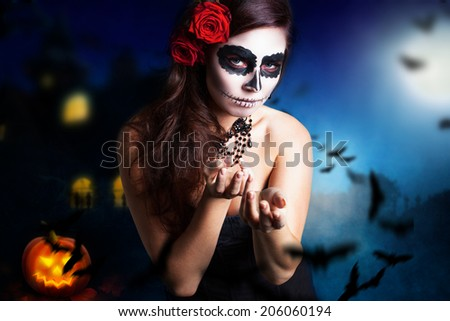 woman with sugar skull styling in front of a halloween background - stock photo