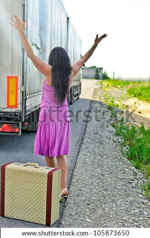 Woman with suitcase hitchhiking a car - stock photo