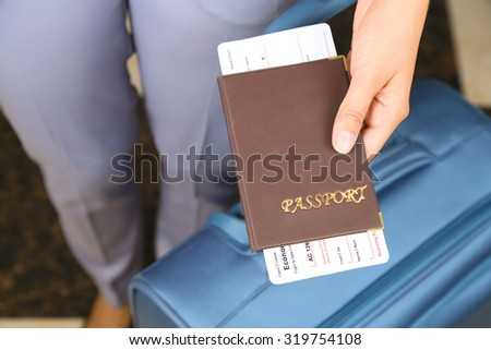 Woman with suitcase holding passport  and tickets close up
