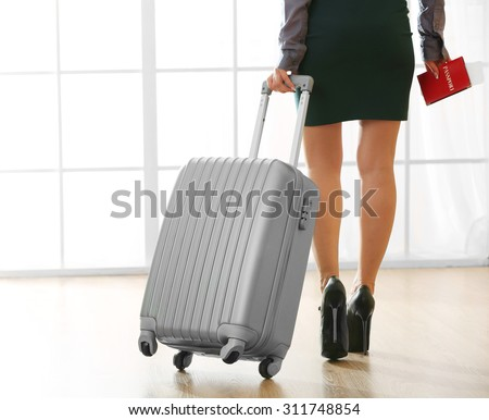 Woman with suitcase in hall - stock photo